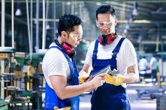 检查工作片断的亚裔工作者在生产设备 库存图片