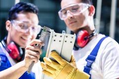 检查工作片断的亚裔工作者在生产设备 免版税库存照片