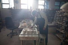 检查工艺产品的男性陶瓷工 免版税库存照片