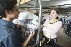 检查干洗的衣裳的顾客与在洗衣店的所有者 免版税图库摄影