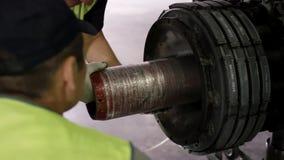 检查底盘的机场工作者 乘客飞机的引擎和底盘在重的维护下的 工程师检查 免版税库存图片