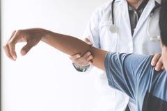 检查患者的医生与手肘确定不适的原因 库存图片