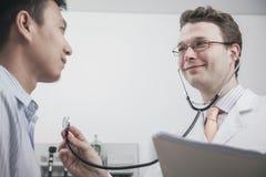 检查患者的心跳的微笑的医生与听诊器 免版税库存图片