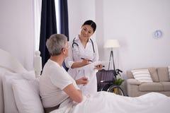 检查患者的护士在床上 图库摄影