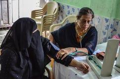 检查患者的血压的一位女性医生在一个医疗阵营期间 免版税库存照片