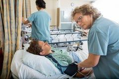 检查患者的血压的护士 免版税图库摄影