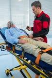 检查患者的血压医务人员 图库摄影