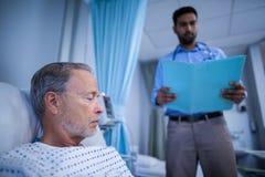 检查患者的医疗报告医生 免版税库存图片