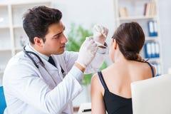 检查患者耳朵的医生在身体检查期间 库存图片
