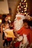 检查愿望的真正的圣诞节父亲被围拢与三g 免版税库存图片