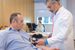 检查成熟男性耐心血压的医生 免版税库存照片