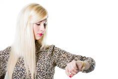 检查手表的美丽的白肤金发的妇女画象 库存照片