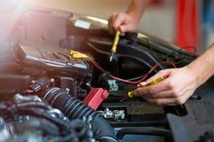 检查技工电压的自动电池汽车 免版税库存照片