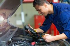 检查技工电压的自动电池汽车 免版税库存图片
