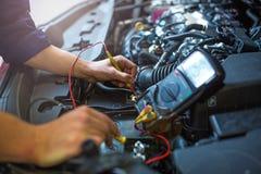 检查技工电压的自动电池汽车 免版税图库摄影