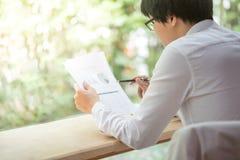 检查报告文件的年轻商人 免版税图库摄影