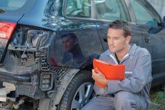 检查损坏的汽车的技工 免版税库存照片