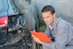 检查损坏的汽车的年轻技工 免版税库存图片