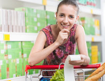 检查收据的妇女在超级市场 免版税库存照片