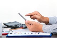 检查数据的一个商人举行手机 免版税图库摄影