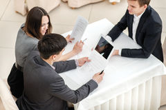检查文件!坐在桌上我的三个年轻人商人 库存图片