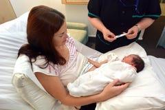 检查新出生的温度的接生婆 免版税库存照片
