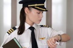 检查时间的专业女性飞行员在他机场 库存图片
