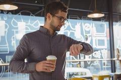 检查时间的商人,当食用咖啡时 免版税库存图片