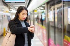 检查时间的女孩,当等待地铁时 库存照片