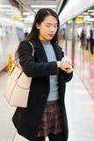 检查时间的女孩,当等待地铁时 图库摄影
