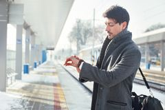 检查时间的年轻人在火车站 免版税库存图片