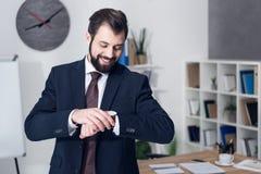 检查时间的微笑的商人画象 免版税图库摄影