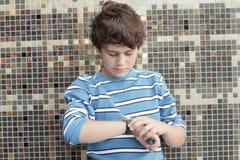 检查时间的男孩 免版税库存图片