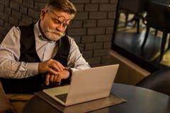 检查时间的资深商人,当坐在桌上与膝上型计算机时 免版税库存图片
