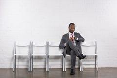 检查时间的非裔美国人的商人,当等待时 图库摄影