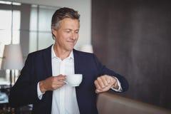 检查时间的商人,当食用咖啡在餐馆时 免版税库存图片