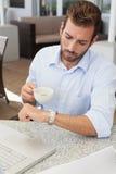 检查时间的皱眉的年轻商人拿着咖啡杯 图库摄影