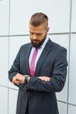 检查时间的年轻紧张的bussinessman,当等待会议时 免版税库存图片