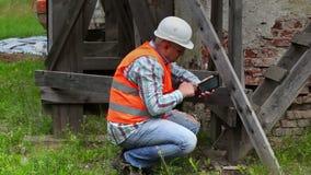 检查木脚手架和使用片剂个人计算机的建筑工人 股票录像