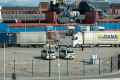 检查来自轮渡在一个晴朗的早晨的拖车的警察在口岸 免版税库存照片