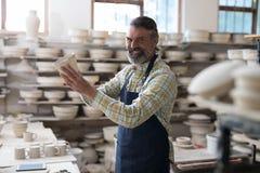 检查杯子的男性陶瓷工 免版税库存图片