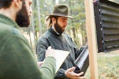 检查树皮甲虫槽孔陷井的林务员 免版税库存照片