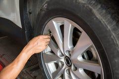 检查气压和填装在轮胎的司机空气紧密  免版税库存图片