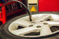 检查气压和填装在轮胎的空气紧密  免版税库存照片