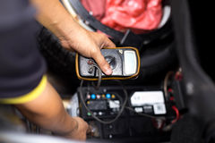 检查汽车电池水平的技工与电压表 免版税图库摄影