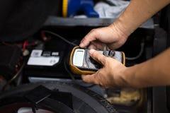 检查汽车电池水平的技工与电压表 免版税库存照片