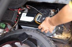 检查汽车电池水平的技工与电压表 库存照片