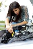 检查汽车被中断的引擎的妇女 免版税库存照片