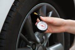 检查汽车轮胎气压的妇女特写镜头与测量仪 免版税库存图片
