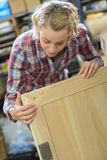 检查测量的年轻女工家具在车间 免版税图库摄影